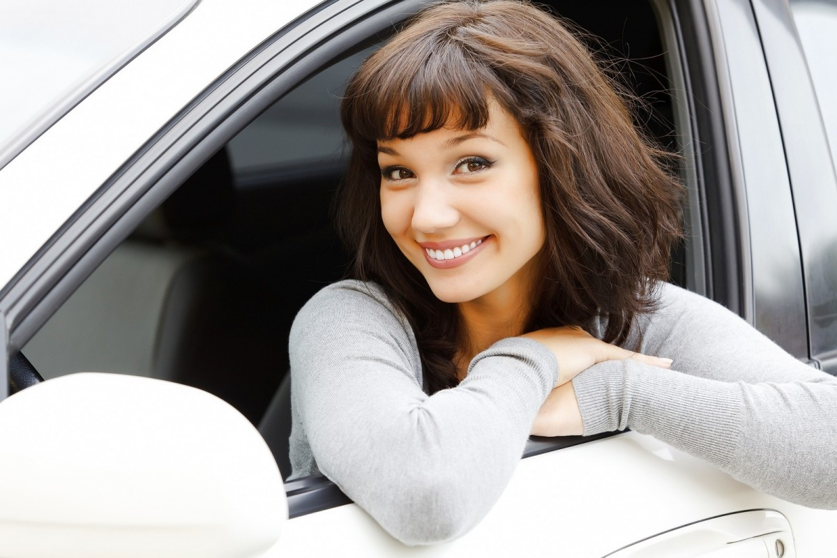 woman smiling on edge of car window